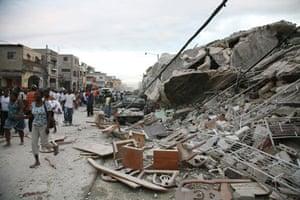 Haiti earthquake: People walk past damaged buildings in Port-au-Prince