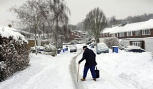 Snow again: An elderly man walks home from the local shop in Hartley Wintney