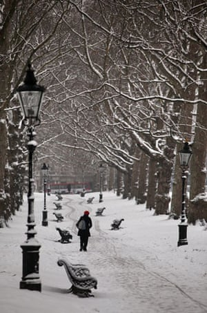 Snow again: A woman makes her way across snow-covered Green Park in London