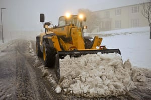 Snow again: A JCB digger clears snow in Princetown, Dartmoor, Devon