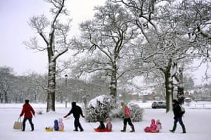 Snow again: Mothers tow children on their sledges across the village green