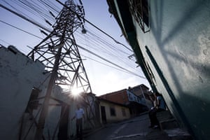 24 hours: People walk along a street in front of an electricity pylon in Caracas