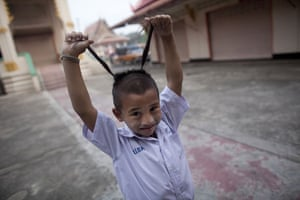 24 hours: Noi Klong, Thailand: A schoolboy shows off his traditional haircut