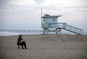 24 hours: A man plays the guitar on Venice Beach in Los Angeles