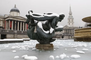 Snowing again: Snow and ice cover one the fountains in London's Trafalgar Square
