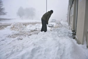 Snowing again: A man clears snow in Princetown, Dartmoor, Devon