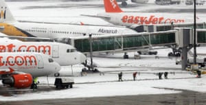 Snowing again: Firemen clear snow from the taxi way at Gatwick Airport