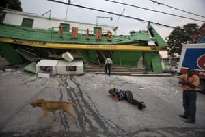 haiti update 3: A woman lies on the ground as others stand outside market Haiti earthquake