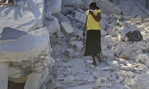 A woman walks among debris in Port-au-Prince, Haiti