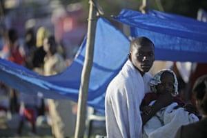 haiti earthquake: A man holds a child in a makeshift camp for earthquake survivors in Haiti