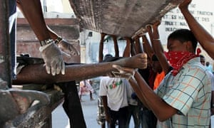 People carry a body to a truck in Port-au-Prince, Haiti