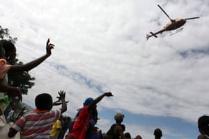 haiti quake: People wave at a helicopter in the center of Port-au-Prince