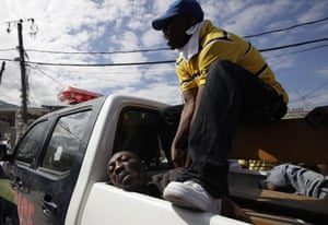 haiti quake: Police guards a detained man accused of trying to steal food in a market
