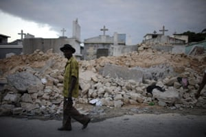 haiti quake: A man walks in front of a destroyed cemetery in Port-au-Prince