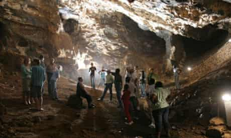 A group of tourists are guided through the Sterkfontein Caves in South Africa