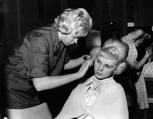 Teenage Hair: A hairdresser finishes a beehive hairstyle on a teenage girl
