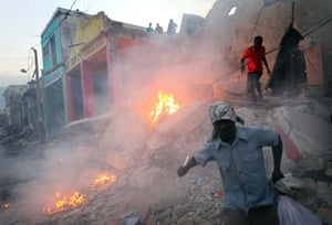 Lawless Haiti: Looters take what they can from a building destroyed in the earthquake