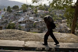 Lawless Haiti: A Haitian man carries his possessions past a destroyed neighbourhood
