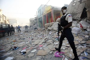 Lawless Haiti: A police officer patrols downtown Port-au-Prince to discourage looting