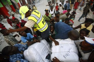 Lawless Haiti: A Haitian police officer tries to stop people from taking away bundles