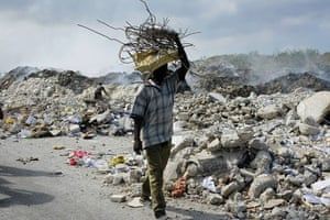 Lawless Haiti: A man carries a bundle of metal bars salvaged from the rubble
