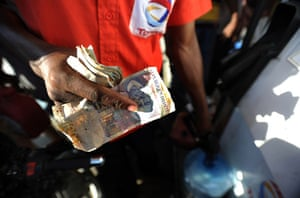 Lawless Haiti: A Haitian fueling station attendant holds a wad of money
