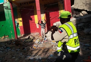 Lawless Haiti: A Haitian police officer points a rifle at a man during a looting spree