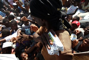 Lawless Haiti: Residents reach out to receive food distributed by UN World Food Program