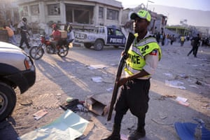 Lawless Haiti: A Haitian national police officer on patrol after firing on looters