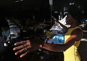 Lawless Haiti: A woman prays over her daughter's bed at a field hospital