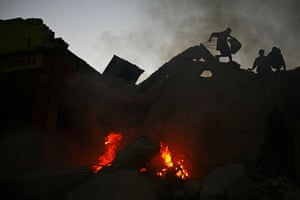 Lawless Haiti: Scavengers walk over the rubble of quake-damaged buildings Port-au-Prince