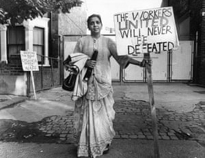Jayaben Desai: A woman stands to camera alone holding handbag, coat and placard