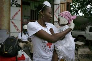 Haiti Aid: Red Cross volunteer Miname Glaude holding Michel Laurent