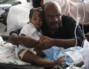 Haiti Aid: A man comforts Desie Ulachine, 7, at a hospital