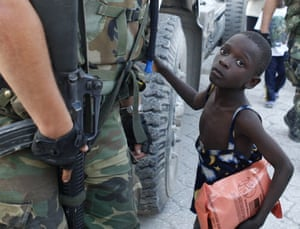 Haiti Aid: A child stands beside a soldier