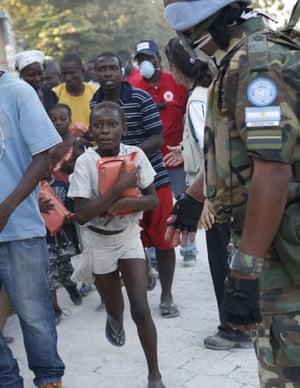Haiti Aid: A boy runs after getting humanitarian aid