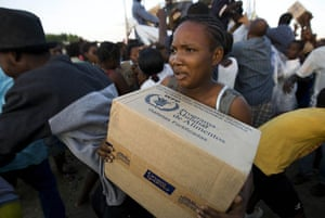 Haiti Aid: A Haitian woman struggles with her box of food