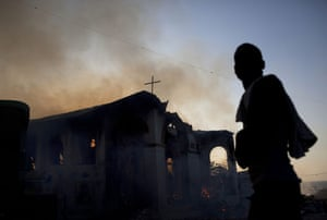 Haiti Aid: man stands in front of a burning church