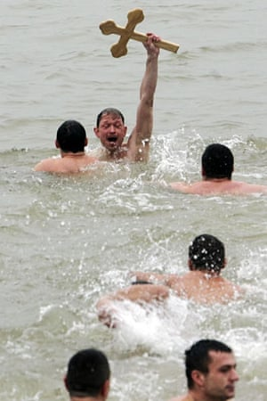 Orthodox Epiphany : Jovan Didier, 44, lifts up a wooden cross