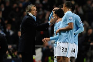 City v United: Tevez receives an appreciative tap on the cheek from Mancini