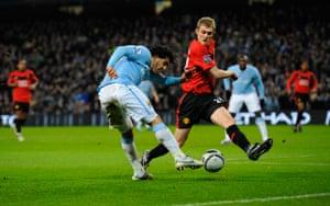 City v United: Tevez fires a shot goalbound despite the close attention of Fletcher