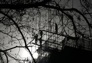 24 hours in pictures: Workers install scaffolding at a construction site in Beijing