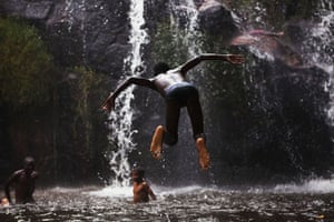 24 hours in pictures: Huila, Angola: A boy jumps into a pool below a waterfall