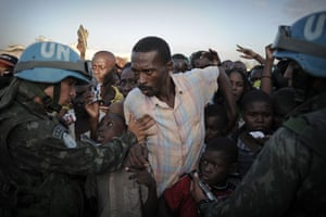 24 hours in pictures: Port-au-Prince, Haiti: People queue for aid at a military airfield
