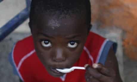 A Haitian child eats a free meal received from a local restaurant in Port-au-Prince
