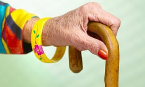 Older woman's hand on a walking stick