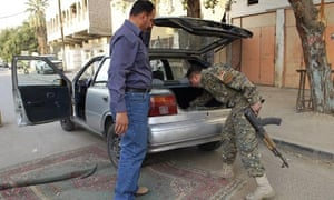 A member of the Awakening Council, a Baghdad neighbourhood guard unit, inspects a vehicle