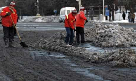 Street cleaners use shovels to remove dirty snow from a main road near Beijing's Tiananmen Square