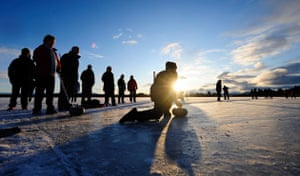 Snow: A curler tests the ice on Lake of Menteith