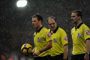 Snow: Referee Mark Clattenburg and his assistants feel the cold